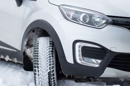 A fragment of the front of an SUV with headlights, front bumper, fog lights on a winter road. Winter driving conditions on a snowy road