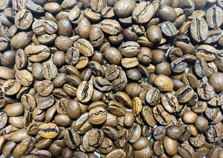 Background of Arabica coffee beans in close-up. Coffee bean texture