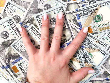 A bunch of dollars in the hands of a close-up. The background is made of dollars. Isolated dollars