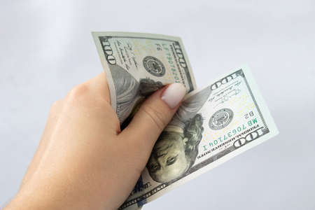 100 dollars in hand close-up on a white isolated background. A hundred-dollar bill