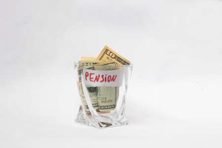 A pile of dollars in a whiskey glass on a white isolated background. Retirement savings in dollars. Pension amount Standard-Bild