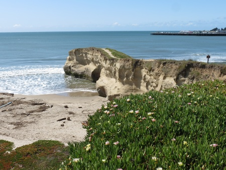 April 5, 2012, Main Beach replenishment project after flood of March. A tunnel or natural bridge through sandstone San Lorenzo Point in Santa Cruz, California, with iceplant in the foreground and blue water of Monterey Bay and wharf in background. Taken w