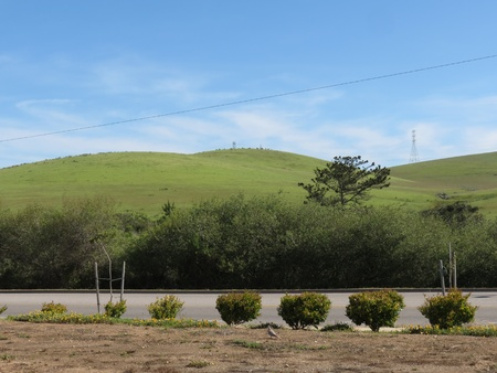 Rolling green hills under blue skies with towers and power line diagonal, highway, trimmed shrubs, and parking lot in foreground Stock Photo - 13299371