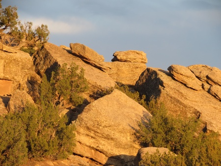 sloping: Rocks in piles on sloping larger rocks lit by late afternoon sun, off I-40 frontage road near Holbrook, Arizona