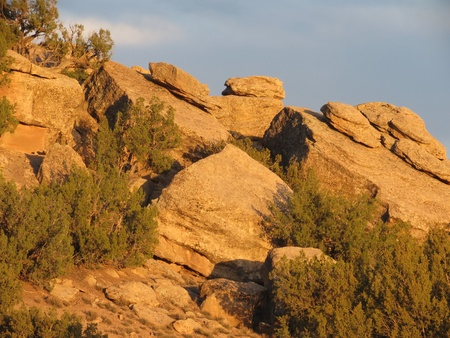 erratic: Rocks in piles on sloping larger rocks lit by late afternoon sun, off I-40 frontage road near Holbrook, Arizona