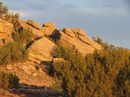 erratic: Rocks in piles on sloping larger rocks, known as erratics, lit by late afternoon sun, off I-40 frontage road near Holbrook, Arizona  Stock Photo