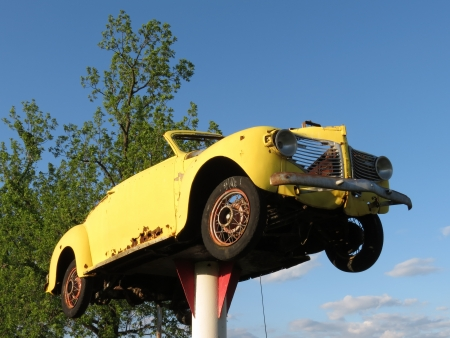 junked: Upward view of yellow roadster auto on rustic pedestal, with sky visible through grill and wheel  Stock Photo