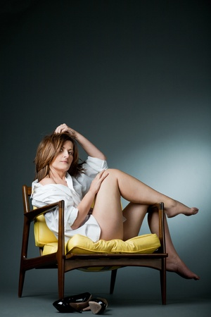 Attractive happy mature woman relaxing on chair.  Stock Photo - 11731637