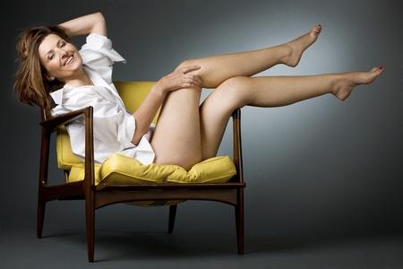 benen: Aantrekkelijk gelukkig volwassen vrouw ontspannen op de stoel. Stockfoto