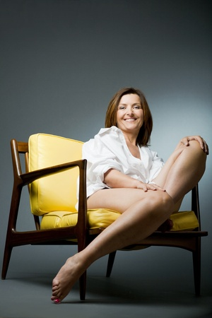 woman  shadow: Attractive happy mature woman relaxing on chair.