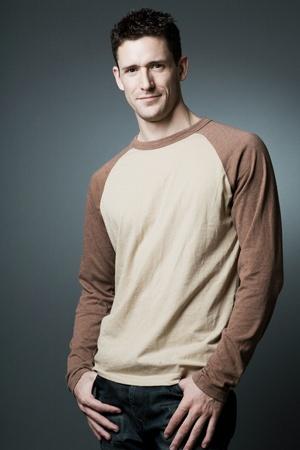 pelo castaño claro: Modelo de moda joven feliz posando sobre fondo gris.