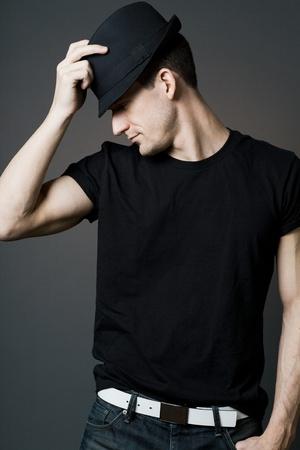 hombre con sombrero: Hombre joven y guapo en camiseta negra que sostiene un sombrero negro. Foto de archivo