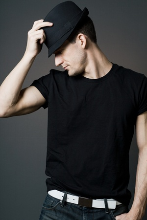 Young handsome man in black shirt holding black hat.