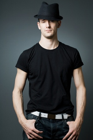 man t shirt: Young handsome man posing in black t-shirt and black hat.