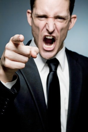 ferocious: Boss points finger at employee and screams. Stock Photo