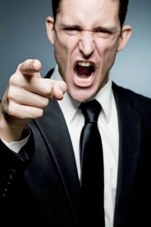 Chef zeigt mit dem Finger auf Mitarbeiter und schreit.