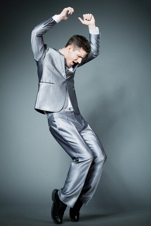 Young handsome businessman in silver suit dancing.