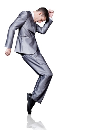 Young handsome businessman in silver suit dancing. Isolated. Stock Photo