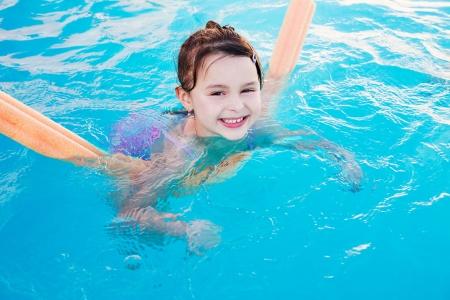 Little girl enjoys summer day in swimming pool.