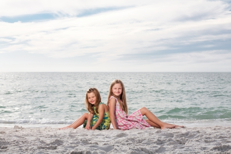 Little happy girls enjoy summer day at the beach. photo