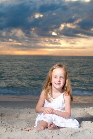Little happy girl enjoys summer day at the beach.