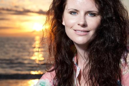 Beautiful young girl enjoys sunset at the beach.