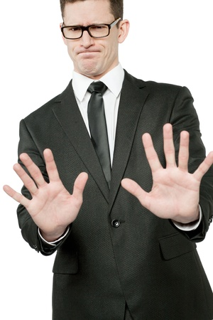 Young handsome businessman in black suit making stop gesture.