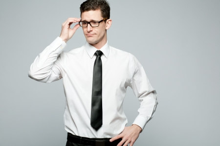 Young handsome businessman in white shirt on gray background. Archivio Fotografico