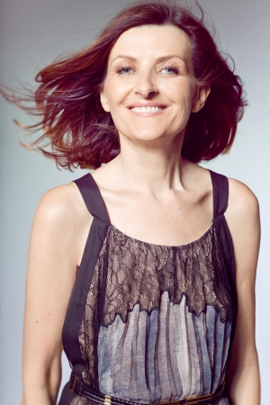 Attractive happy middle-aged woman with curly hair   Archivio Fotografico