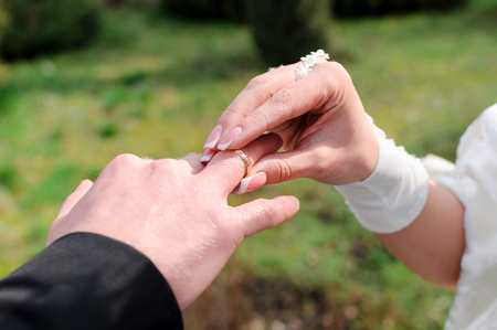 The bride dresses to the groom a ring at a ceremony. Close up of hands.