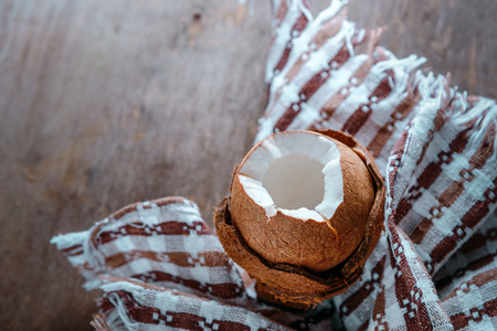Tropical Coconut open on a wooden table with a texture cloth towel kitchen.