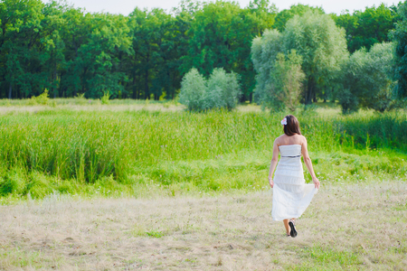 Girl in a pancake white dress on a green meadow back side. The beautiful place for walk. Relaxation walk outdoor concept. Warm summer sunny day.