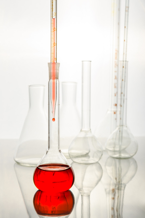 Investigation of a red liquid in chemical research laboratories. Empty and full bottles and vessels. Reklamní fotografie