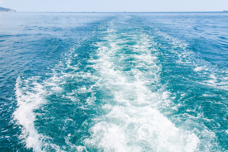 Wake from a boat on the sea in a sunny day in summer. Track of the ship on sea