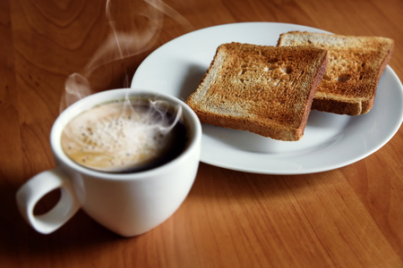 Hot coffee with foam and fresh toast. Morning breakfast.