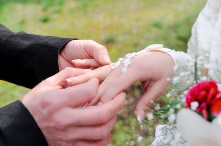 The groom holds a ring on a finger at the bride. A close up of hands during a ceremony.