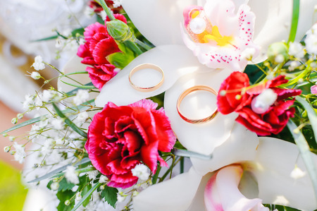 Wedding rings on bridal bouquet. A close up of rings during a ceremony.