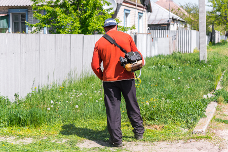 Grass cutting on the backyard. A man with his back in the frame cuts the lawn.