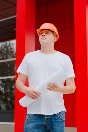 Engineer Outdoor in Helmet Hold Plan in Hand Stock Photo
