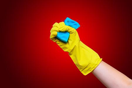 lavar platos: La mano en el guante amarillo comprime la esponja para lavarse.