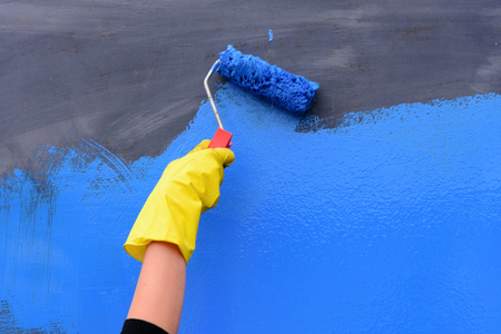 Painter arm in yellow glove painting a wall with paint roller blue color with copy space Stock Photo