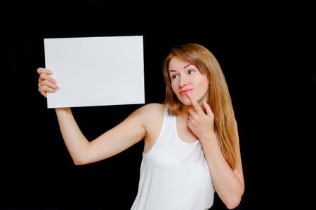 The girl in a light undershirt against a dark background playfully holds the announcement in hand. White copy space blank in hand woman.