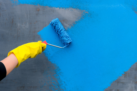 Hand in yellow glove and Paint roller applying blue paint on gray wall, home improvements, horizontal view with copy space.