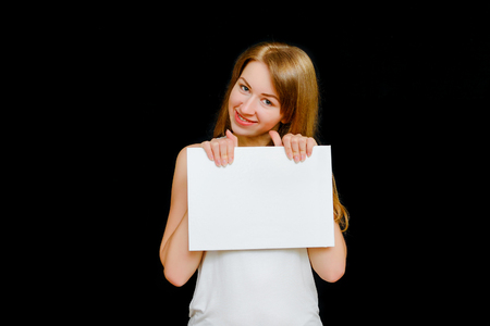 advertize: The lovely girl in a light undershirt against a dark background holds an advertizing board in hand. A white billboard the place for the text.