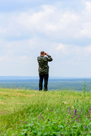 The adult man in a camouflage looks in the binocular at the nature Stock Photo