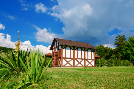 Small beautiful lodge with a lawn. Summer day in the park in the country. Rural landscape with