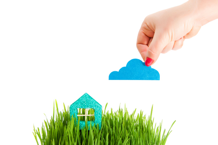 The female hand keeps a cloud over the house in a grass. Little house on the green grass isolated on a white background. Concept of protection of real estate. Insurance of own real estate.