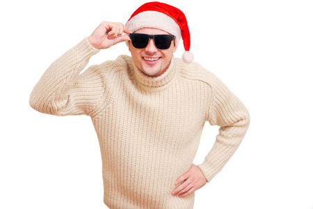 Smiling Man Santa heading and sunglasses. Young man in a knitted sweater good mood. Studia isolate on white background.