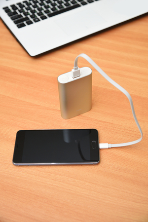 adapters: Power bank charging smart phone on wood table. Digital electronic devices on wood table.