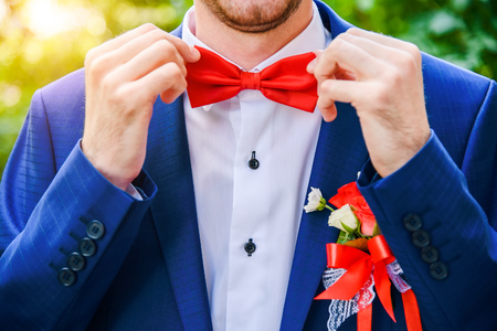 corrects: The groom in a blue suit corrects a red butterfly. Attractive fashionable groom. The man with a beard in a suit. Stock Photo
